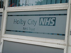A partially frosted window which reads 'Holby City NHS, NHS Trust'