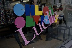 "A storefront window with a large slanted ""Luella"" superimposed over a multi-colored name logo that reads ""CHLOË SEVIGNY""."