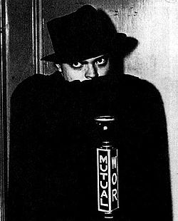"Man in black hat concealing the bottom of his face with a black cape and gazing fiercely. A microphone in front bears the word ""Mutual"" and the call letters ""WOR""."