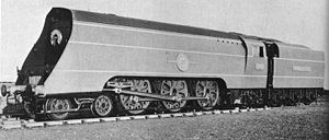A posed side-and-front view of a large 4-6-2 steam locomotive with a tender. The locomotive boiler is hidden by a casing of flat metal side sheets.